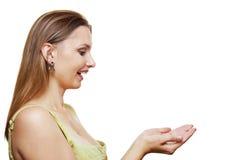 Frau, die etwas auf der Palme ihrer Hand zeigt Stockfotografie