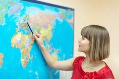 Frau, die etwas auf Weltkarte zeigt Stockbild