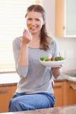 Frau, die etwas Salat in der Küche isst Lizenzfreie Stockbilder