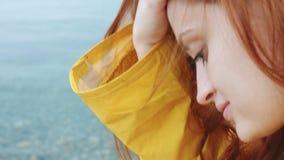 Frau, die etwas am Telefon auf der Seeküste schaut stock video