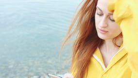 Frau, die etwas am Telefon auf der Seeküste schaut stock footage