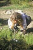 Frau, die etwas Trinkwasser auf ihrem Gesicht von einem Fluss spritzt Lizenzfreies Stockfoto
