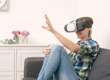 Frau, die etwas unter Verwendung der Kopfhörergläser der virtuellen Realität berührt Stockfoto