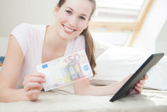 Frau, die 50 Euro- und Tablettengerät hält Stockbild