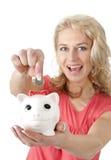Frau, die Euromünze in Sparschwein einsetzt Stockfoto