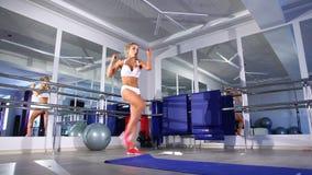 Frau, die für das Trainieren in einer Turnhalle aufwärmt stock footage