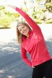 Frau, die für einen Lauf aufwärmt Stockfotografie