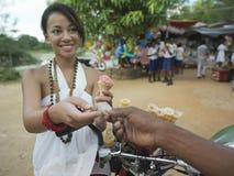 Frau, die für Eiscreme am Straßenmarkt- zahlt Lizenzfreies Stockfoto