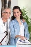 Frau, die für Großmutter bügelt stockfotos