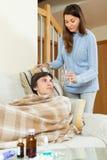 Frau, die für kranken Ehemann sich interessiert Stockbild