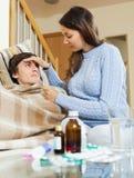 Frau, die für kranken Kerl den hohe Temperatur sich interessiert Lizenzfreie Stockfotografie