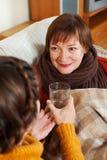 Frau, die für unwohle ältere Mutter sich interessiert Stockfotografie