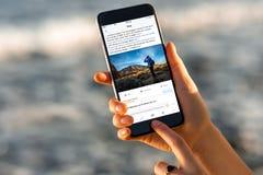 Frau, die Facebook-Nachrichten mit neuem iPhone aufpasst Lizenzfreie Stockbilder