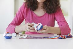 Frau, die fantasiereiche Babyschuhe an ihrem Studio herstellt Stockfotografie