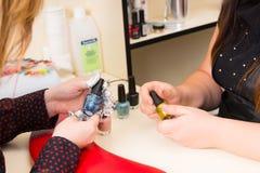 Frau, die Farbe des Nagellacks für Maniküre wählt Stockfotos