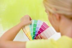Frau, die Farbe für Wand wählt Stockbilder