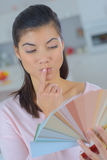 Frau, die Farben wählt und Farbmuster hält Lizenzfreie Stockfotografie