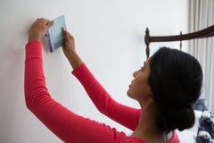 Frau, die Farbmuster durch Wand hält Lizenzfreie Stockfotografie