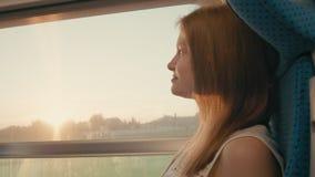 Frau, die am Fenster bei Sonnenuntergang und dann zur Kamera reist mit dem Zug schaut stock footage