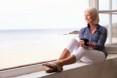 Frau, die am Fenster sitzt und schöne Strand-Ansicht betrachtet Stockbild