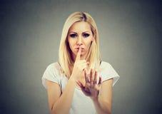 Frau, die Finger auf Lippen in beruhigender Geste hält stockbilder