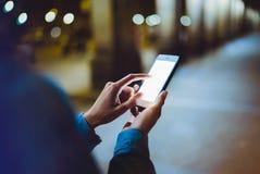 Frau, die Finger auf Smartphone des leeren Bildschirms auf Hintergrund bokeh Licht in der Nachtatmosphärischen Stadt, Hippie Blog stockfotografie