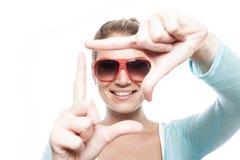 Frau, die Fingerrahmen macht Stockfoto