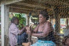 Frau, die Fischernetz repariert Stockfoto
