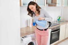 Frau, die flüssiges Reinigungsmittel in der Flaschenkapsel gießt Lizenzfreie Stockfotografie