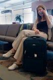 Frau, die am Flughafen-Gatter spricht auf Mobiltelefon wartet Lizenzfreie Stockfotos