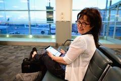 Frau, die am Flughafen wartet Stockfotografie