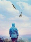 Frau, die Flugwesenvögel betrachtet Stockfotografie