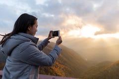 Frau, die Foto auf Berg macht stockbild