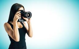 Frau, die Foto auf blauem Hintergrund macht Lizenzfreies Stockfoto