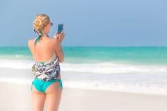 Frau, die Foto auf dem Strand macht Stockfotos