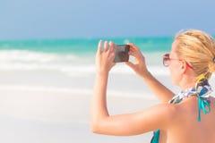 Frau, die Foto auf dem Strand macht Stockbild