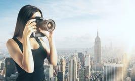 Frau, die Foto auf Stadthintergrund macht Stockfotografie