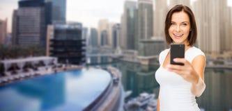 Frau, die Foto durch Smartphone über Dubai-Stadt macht Stockbild
