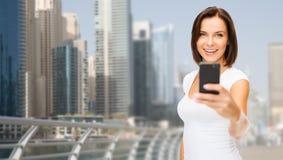 Frau, die Foto durch Smartphone über Dubai-Stadt macht Lizenzfreie Stockfotos