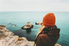 Frau, die Foto durch Smartphone der Seelandschaft macht Stockbild