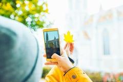 Frau, die Foto an ihrem Telefon der alten Kirche macht Stockfotografie