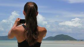Frau, die Foto mit Mobiltelefon auf dem Strand nimmt Mädchen, das Foto auf dem Seehintergrund macht stock video