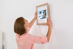 Frau, die Foto-Rahmen auf Wand setzt Stockfoto