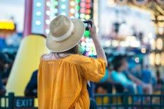 Frau, die Foto am Vergnügungspark während ihrer Reise an den Sommerferien macht stockbild