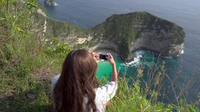 Frau, die Foto vom Ozeanufer in Insel Nusa Penida macht stock video