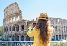 Frau, die Foto von colosseum in Rom, Italien macht Stockfotografie