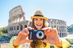 Frau, die Foto vor colosseum in Rom macht Stockfotos
