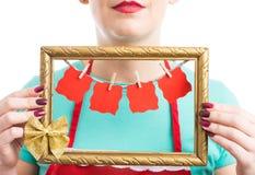 Frau, die Fotorahmen mit hängenden leeren Papieren hält lizenzfreie stockfotografie
