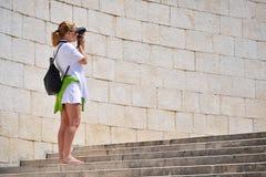 Frau, die Fotos auf der Straße nimmt Stockfotografie