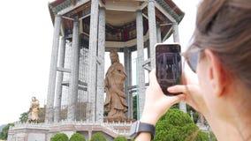 Frau, die Fotos durch Smartphone der Göttin der Statue der Gnade Guanyin oder Guan Yins im buddhistischen Tempel macht Besuchsang stock video